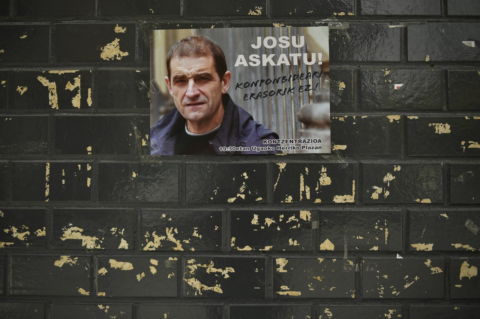 A poster with the face of the former leader of the Basque separatist group ETA, Josu Ternera, seen on a wall in his hometown of Ugao-Miraballes, northern Spain, May 16, 2019. (AP Photo)