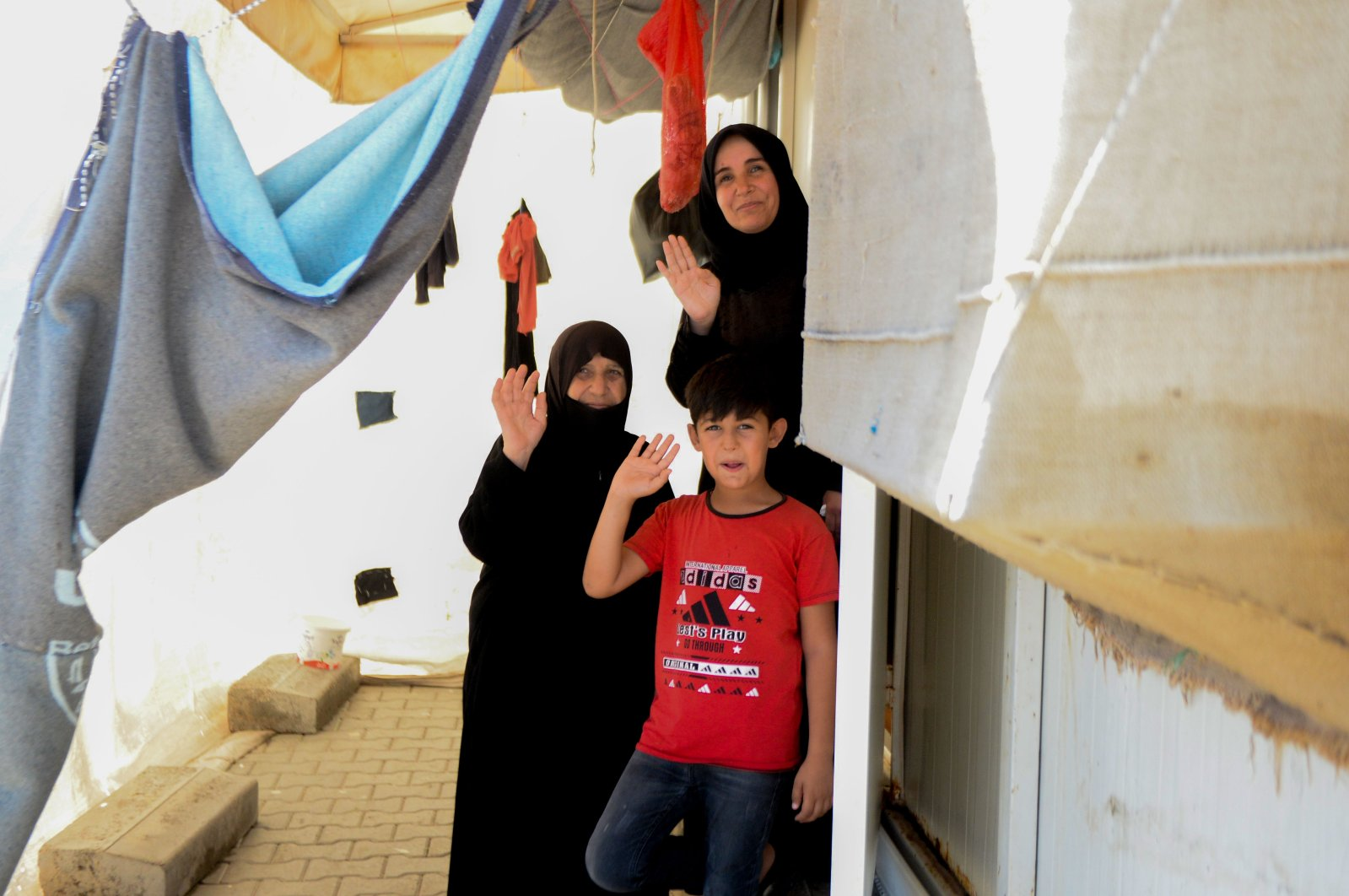 Two women and a boy wave at the door of their house in Elbeyli refugee camp, in Kilis, southern Turkey, July 27, 2020. (AA Photo)