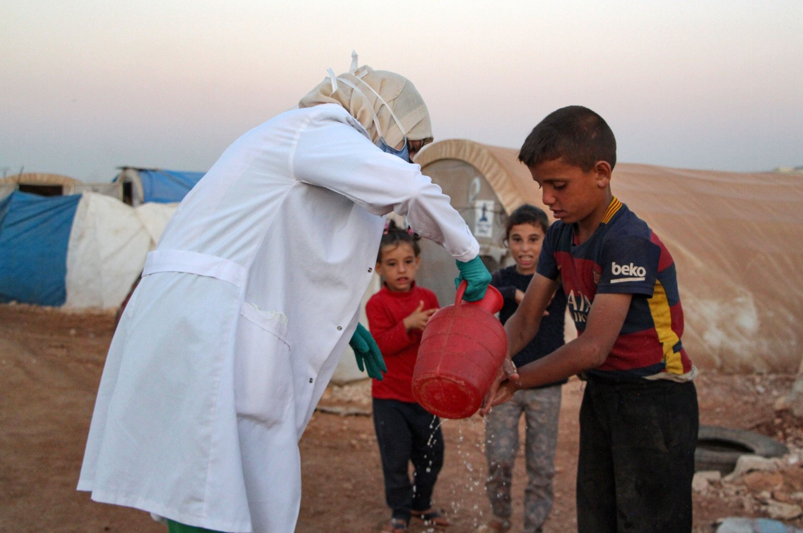 A Syrian doctor, under her own initiative, instructs children how to properly wash their hands during the coronavirus pandemic, east of the Turkish-Syrian border in the Janid displacement camp near the town of Dana, northwestern Idlib province, Syria, July 26, 2020. (AFP Photo)