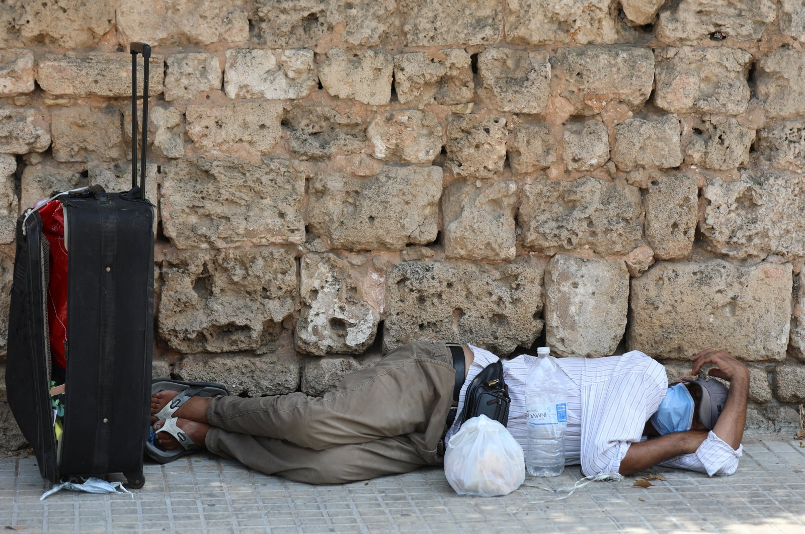 A man lies on the ground as he wears a face mask to prevent the spread of the coronavirus, Beirut, Lebanon, July 28, 2020. (REUTERS Photo)