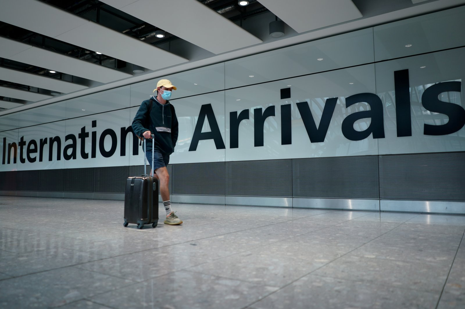 A traveler wearing a face mask walks in Terminal 5 at Heathrow Airport, as the spread of the coronavirus continues, in London, Britain, July 26, 2020. (Reuters Photo)