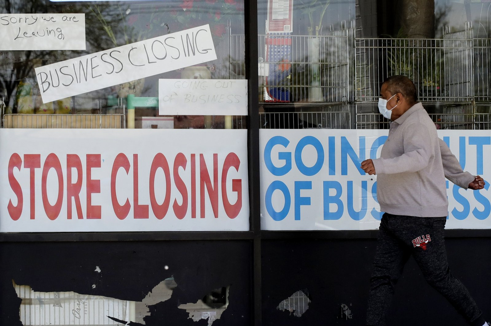 A man walks past signs of a store going out of business during the coronavirus outbreak in Niles, Illinois, U.S., May 21, 2020. (AP Photo)