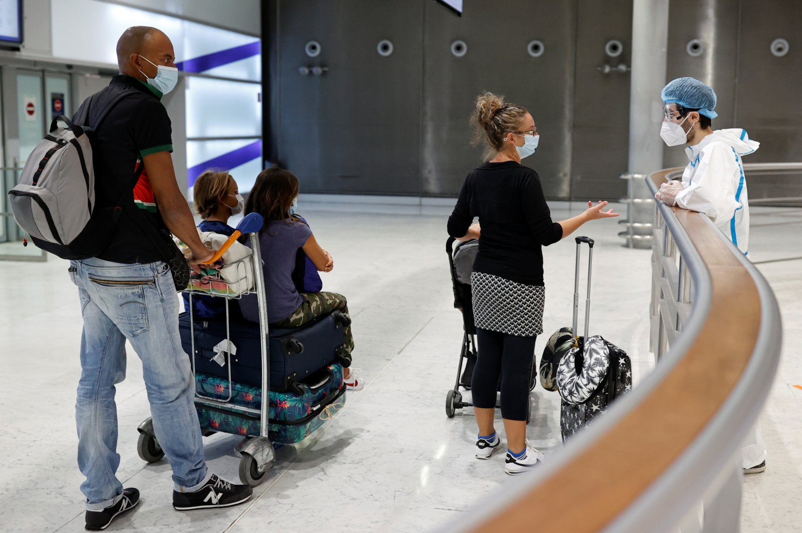 A health worker wearing protective gear talks with passengers to be tested for COVID-19 on arrival at Charles de Gaulle airport amid the coronavirus disease (COVID-19) outbreak, in Roissy, near Paris, France on July 31, 2020. (Reuters Photo)