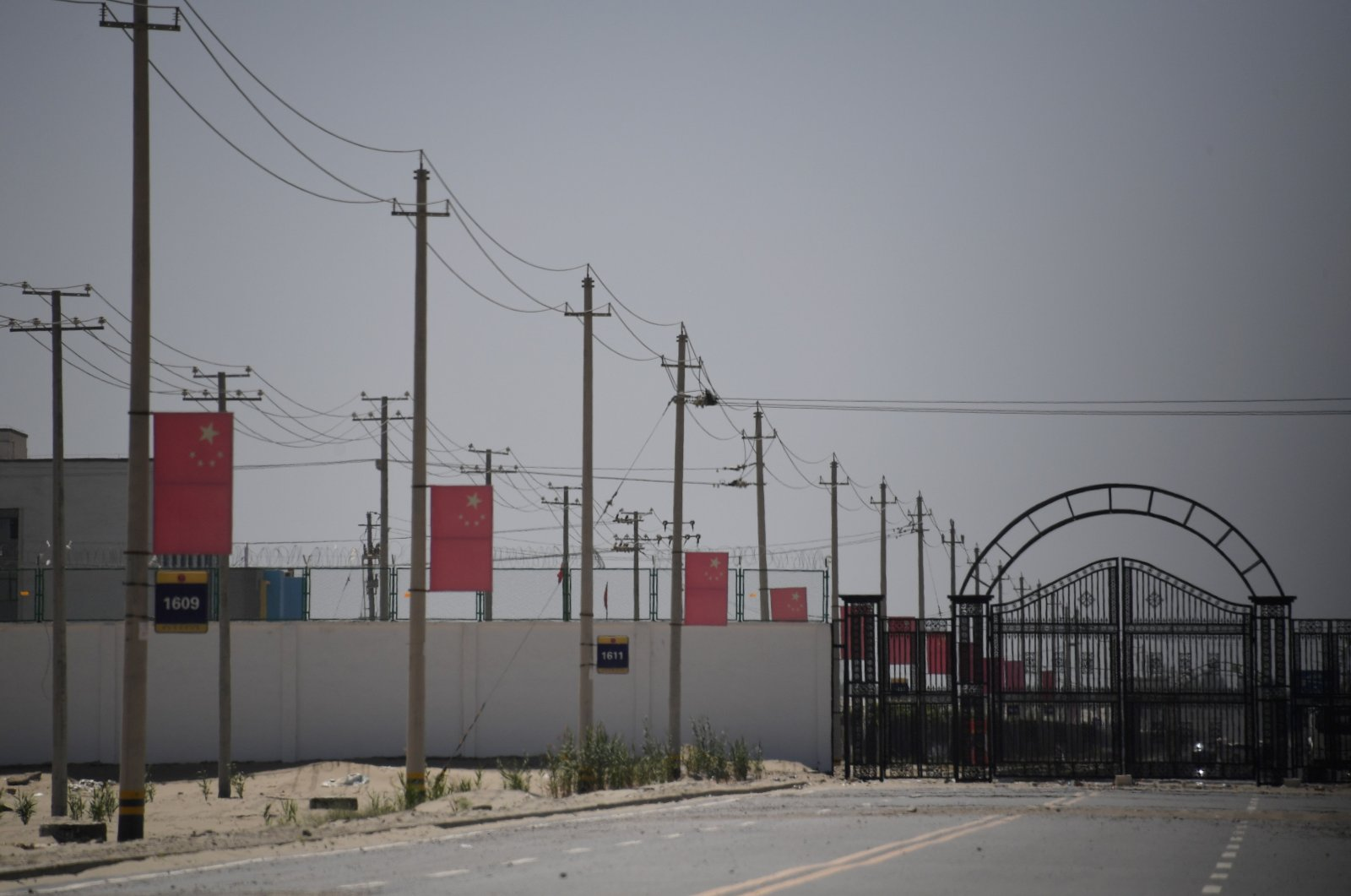 Chinese flags on a road leading to a facility believed to be a re-education camp where mostly Muslim ethnic minorities are detained, on the outskirts of Hotan, Xinjiang Uighur Autonomous Region, northwest China, May 31, 2019. (AFP File Photo)
