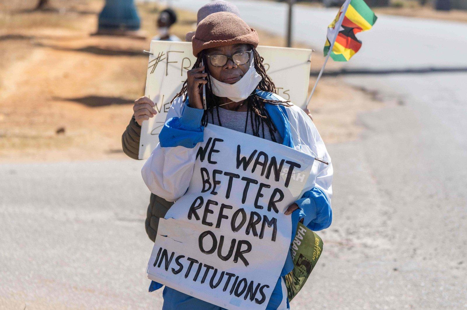 Zimbabwean novelist Tsitsi Dangarembga holds a placard during an anti-corruption protest march along Borrowdale road,  Harare, Zimbabwe, July 31, 2020. (Photo by ZINYANGE AUNTONY / AFP)