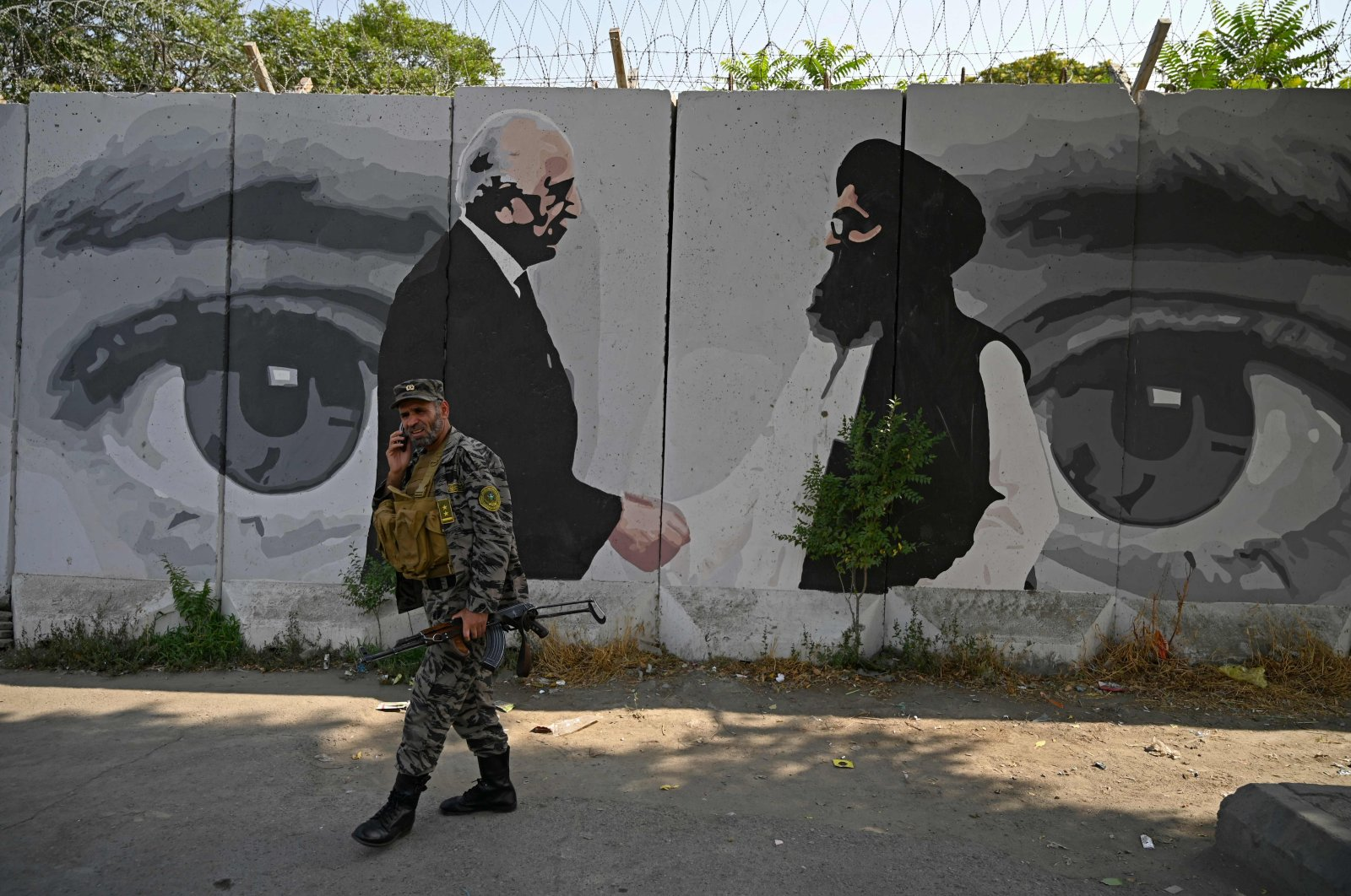 A security personnel walks past a wall mural with images of U.S. Special Representative for Afghanistan Reconciliation Zalmay Khalilzad (L) and Taliban co-founder Mullah Abdul Ghani Baradar (R), Kabul, Afghanistan, July 31, 2020. (AFP Photo)