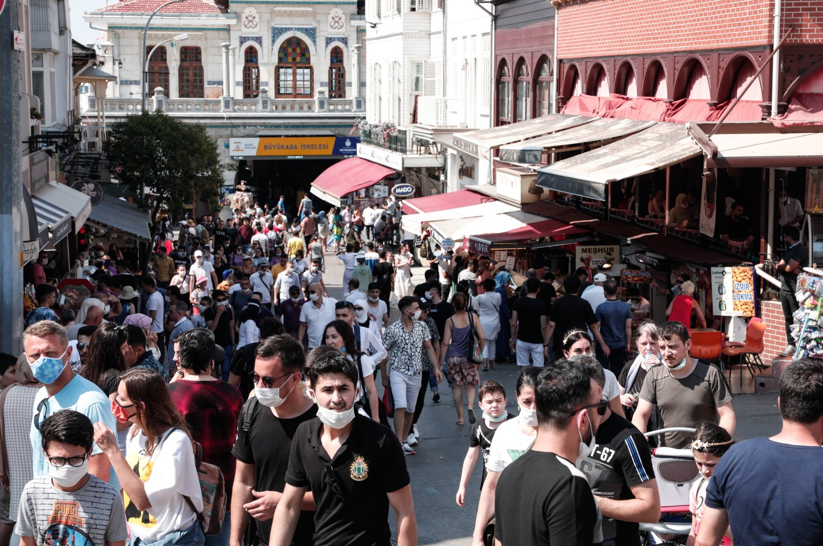 Citizens, many of them not so wary of social distancing and proper wearing of masks in Istanbul's Büyükada, August 1, 2020 (DHA Photo)