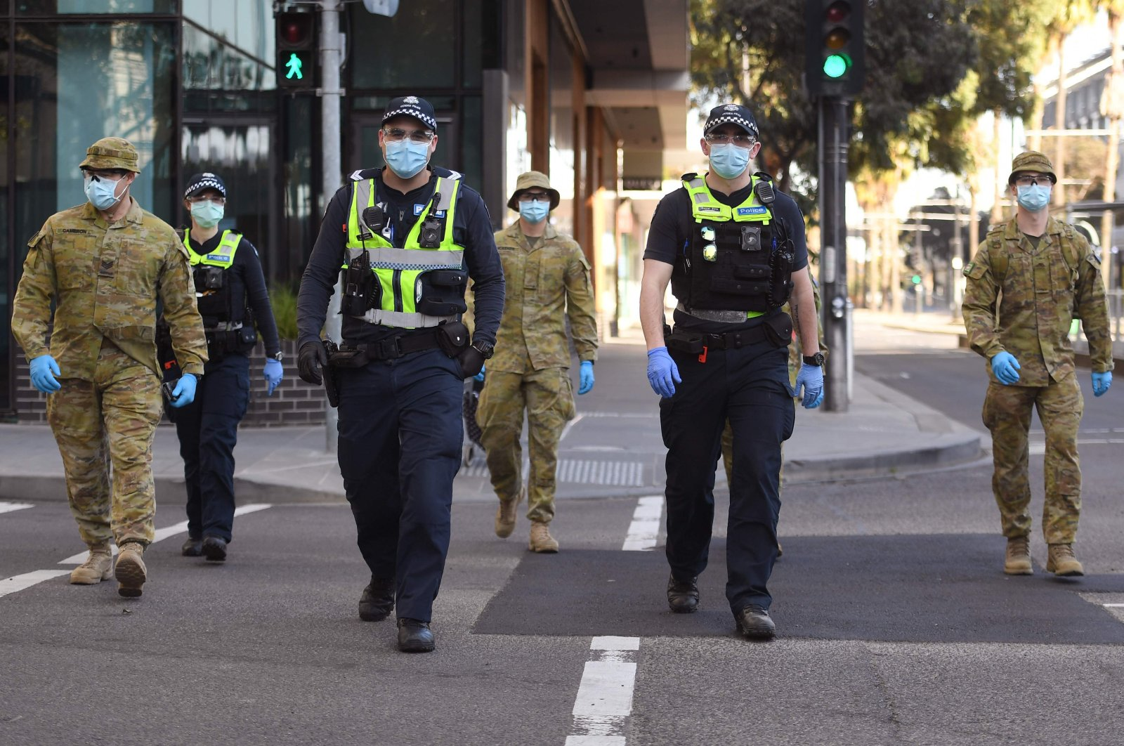A group of police and soldiers patrol the Docklands area of Melbourne on August 2, 2020, after the announcement of new restrictions to curb the spread of the COVID-19 coronavirus. (AFP Photo)