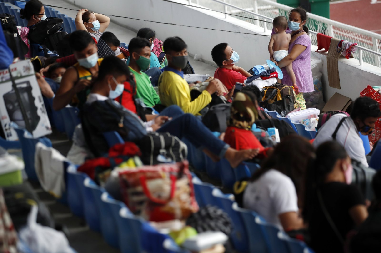 Stranded Filipino villagers with their belongings take shelter inside a gymnasium during the coronavirus and COVID-19 disease pandemic in Manila, Philippines, 29 July 2020. (EPA Photo)
