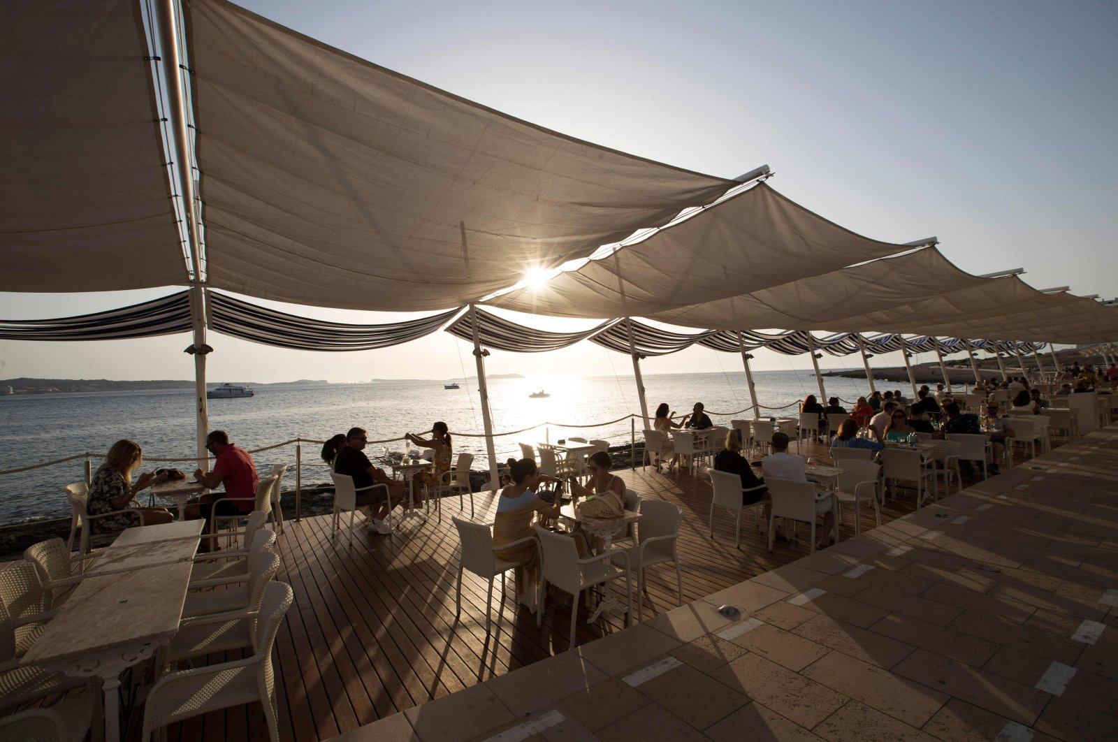 """Tourists sit at the terrasse bar """"Cafe del Mar"""" in Sant Antoni de Portmany, Ibiza, on July 30, 2020. (AFP Photo)"""