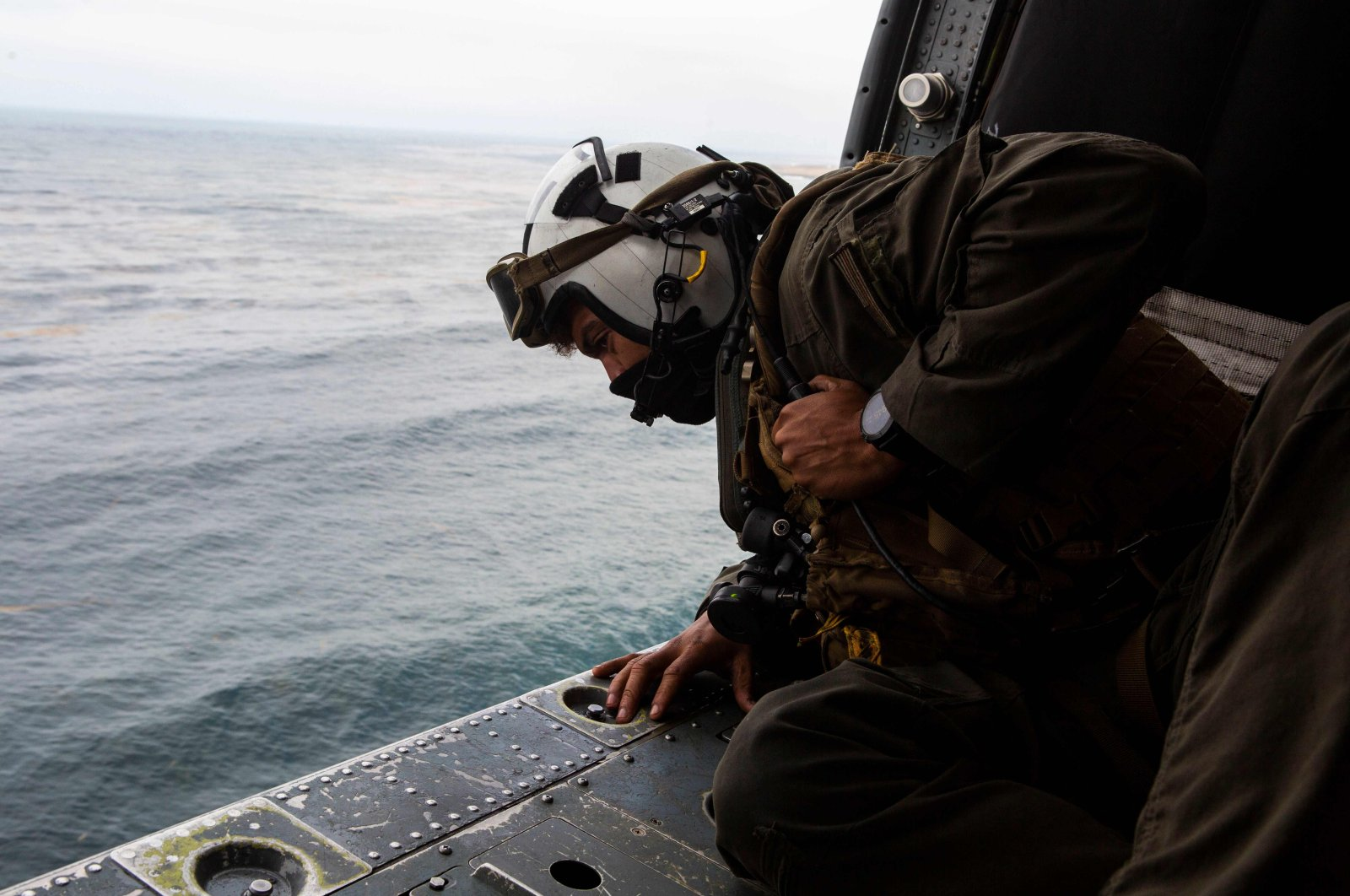 Naval Air Crewman (Helicopter) 2nd Class Joseph Rivera, a search and rescue swimmer assigned to the amphibious assault ship USS Makin Island (LHD-8) looks out of a U.S. Navy MH-60 Seahawk while conducting search and rescue relief operations following an AAV-P7/A1 assault amphibious vehicle mishap off the coast of Southern California, July 30, 2020. (U.S. Marine Corps photo via AFP)