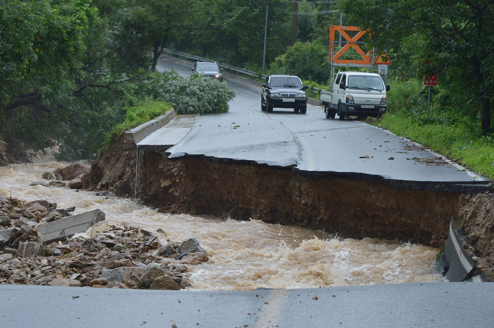 A road that collapsed due to heavy rain is seen in Chungju, South Korea, Aug. 2, 2020. (EPA Photo)