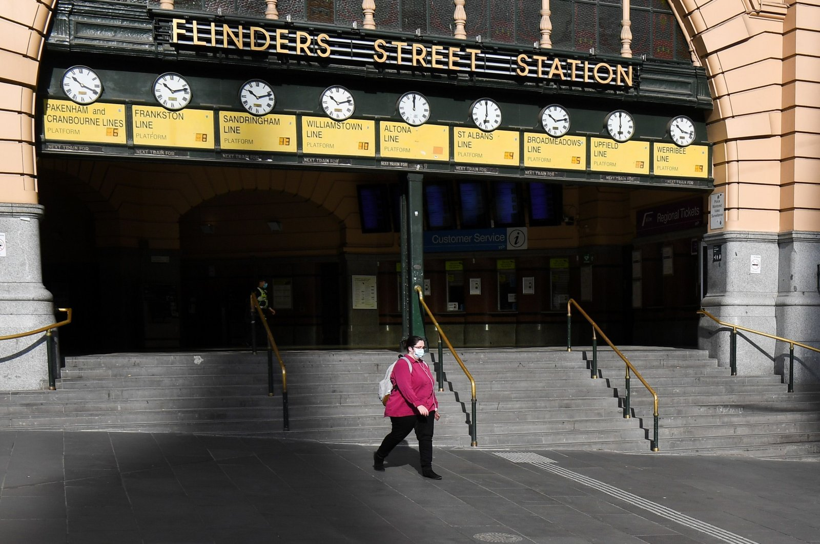A woman walks out of a near-deserted Flinders Street Station in Melbourne on Aug. 3, 2020, after the state announced new restrictions as the city battles fresh outbreaks of the coronavirus. (AFP Photo)