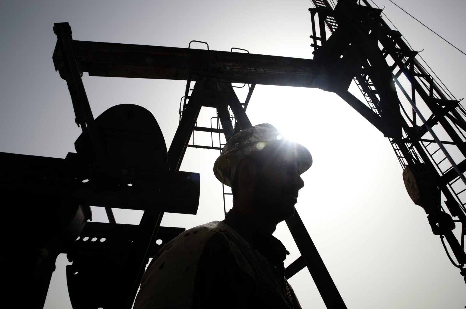 A silhouetted Syrian oil worker stands next to a pump at an oil field controlled by a YPG-linked group in Rmeilan, Hassakeh province, Syria, March 27, 2018. (AP File Photo)