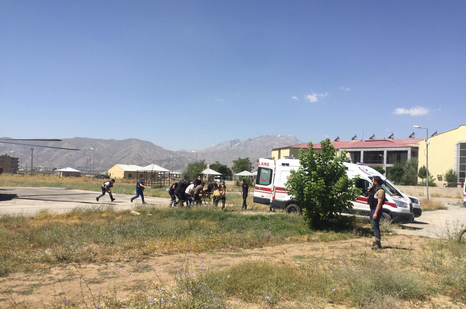 A person injured in a minibus accident is carried to an ambulance in Hakkari province's Yüksekova district, southeastern Turkey, Aug. 3, 2020. (DHA Photo)