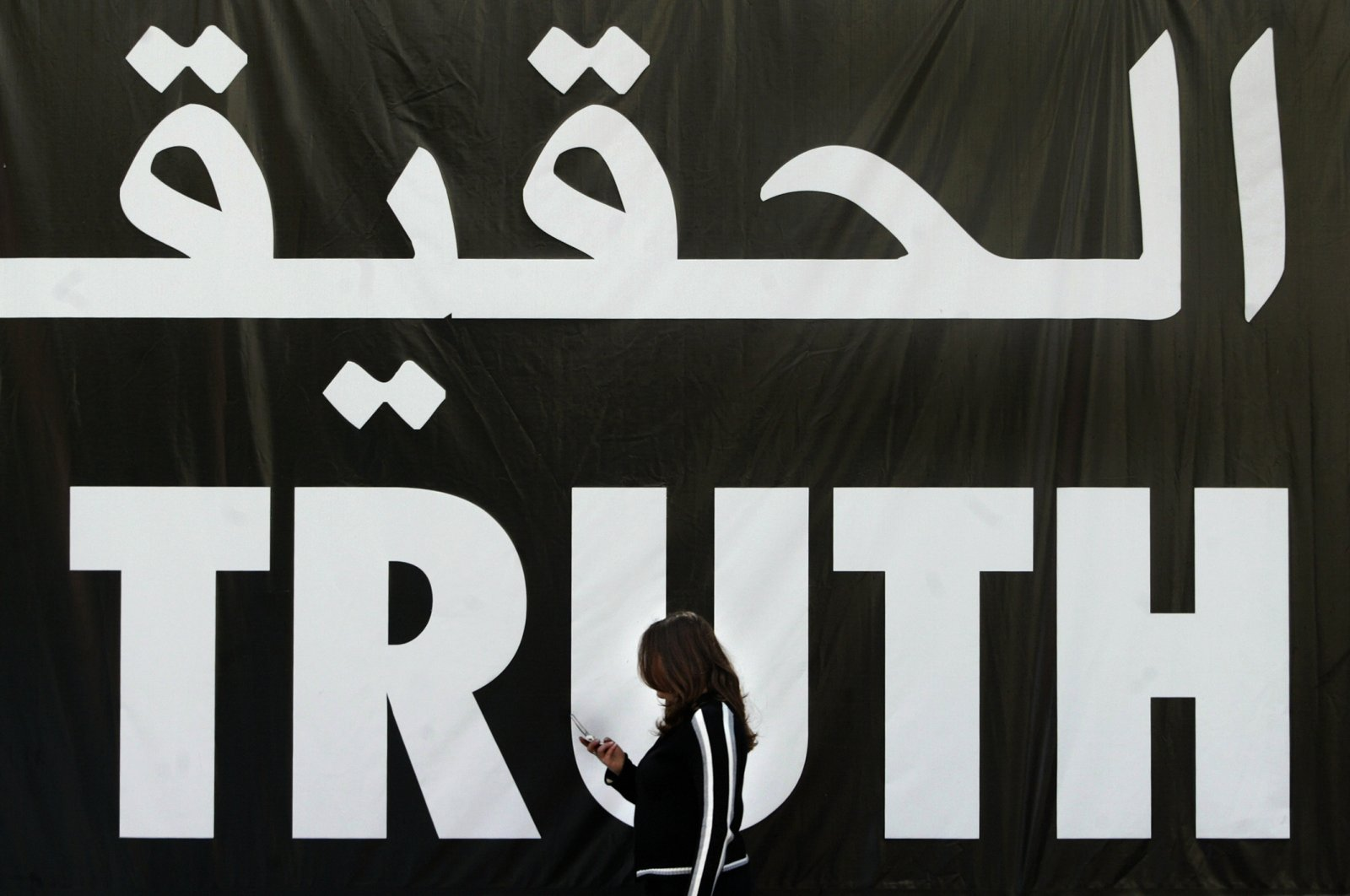"""A Lebanese woman uses her mobile phone as she walks past a giant banner reading """"truth"""" in Arabic and English, Beirut, Apr. 5, 2005. (AFP Photo)"""