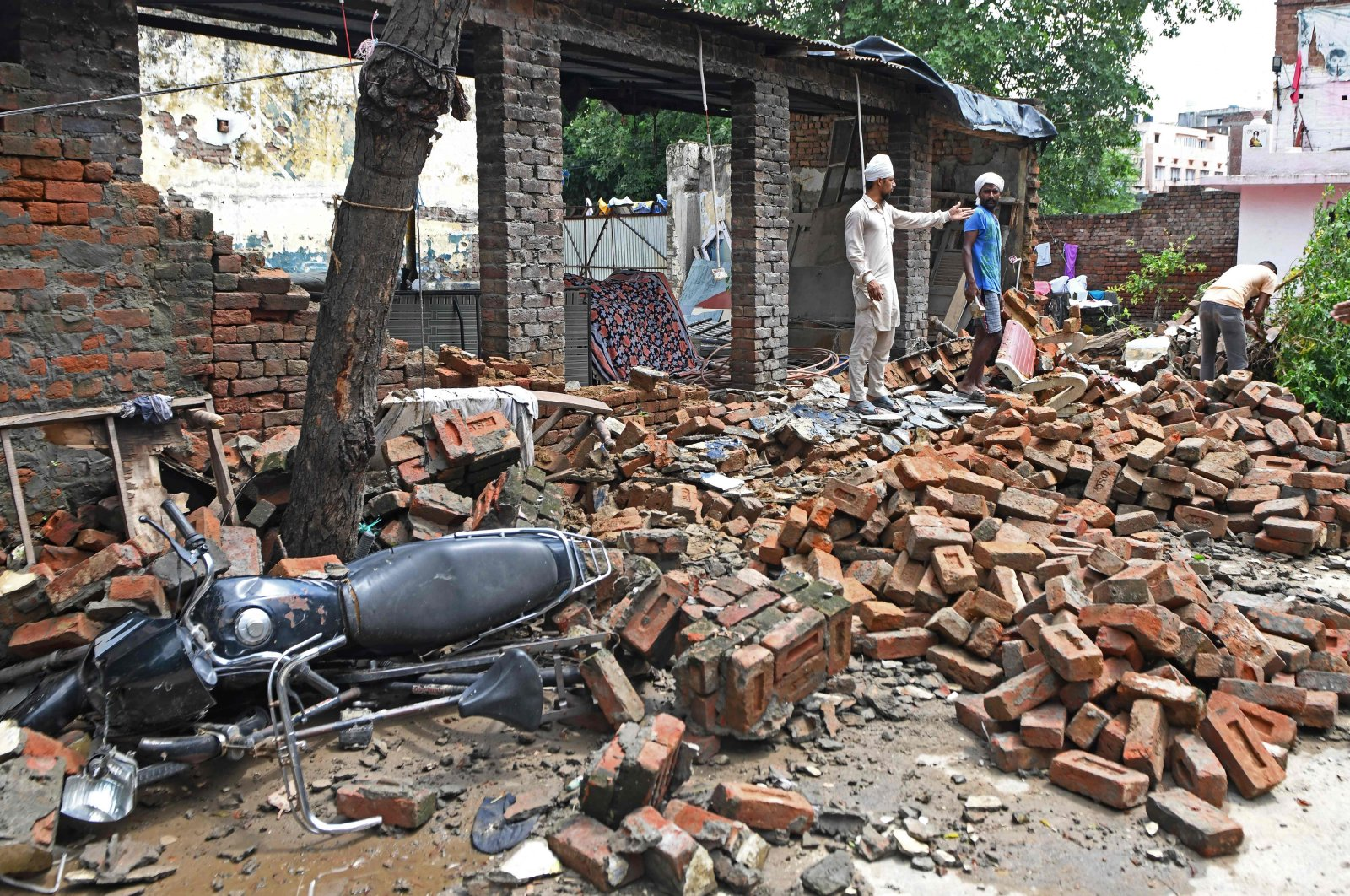 Workers stand amid the debris of a collapsed house wall after heavy monsoon rains, Amritsar, northwestern India, July 30, 2020. (AFP Photo)