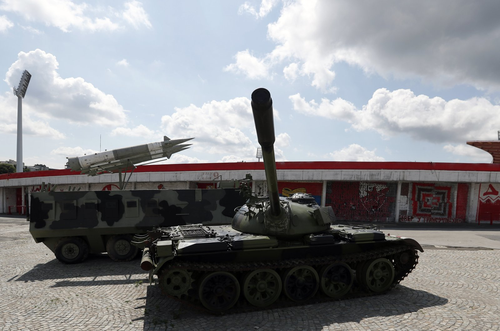 A former Yugoslav army T-55 battle tank adorned with the club's trademark red and white emblem and a model of an anti-aircraft rocket system parked in front of northern grandstand of Rajko Mitic stadium in Belgrade, Serbia, June 20, 2020. (AP Photo)