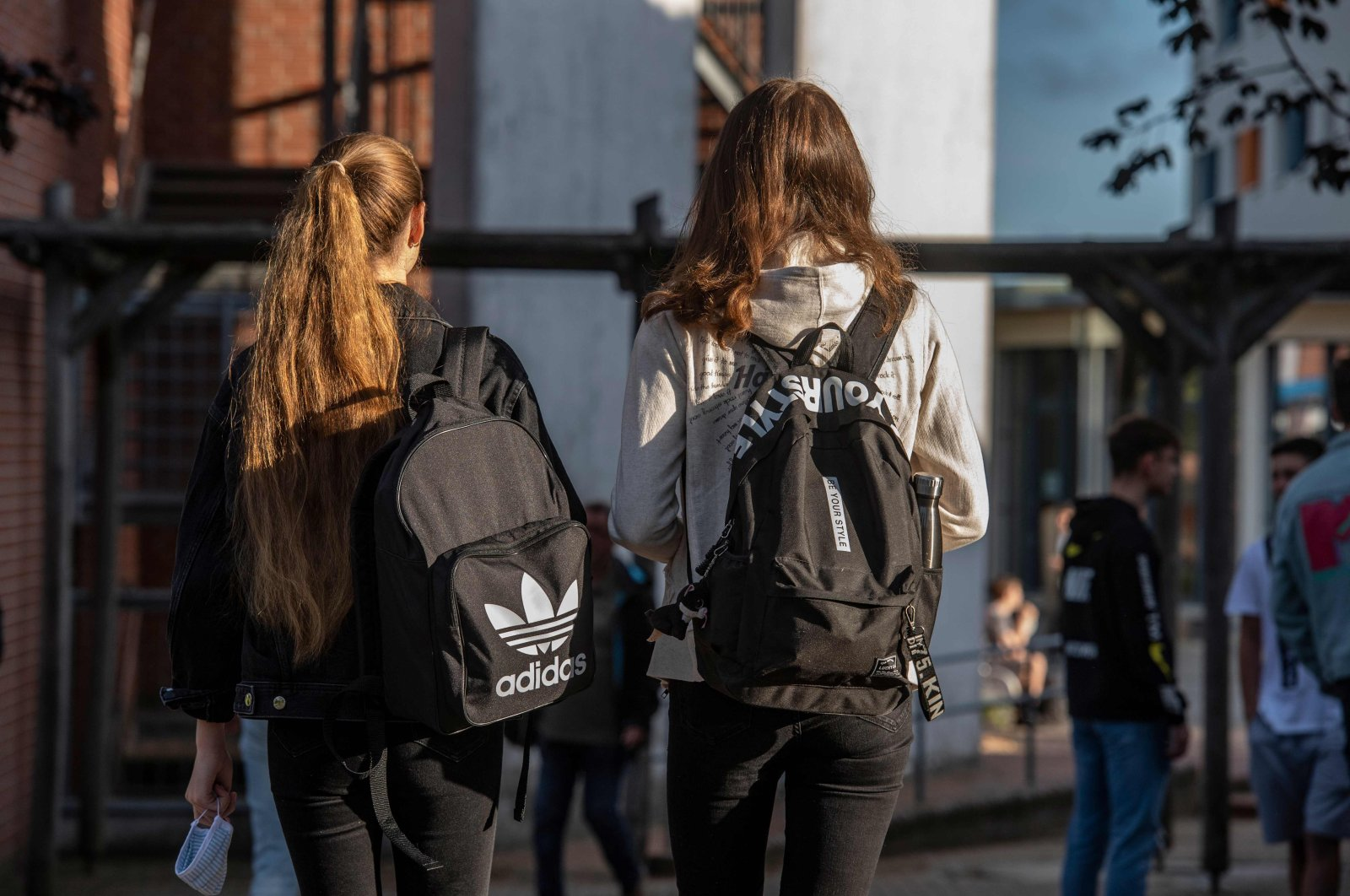 A student (L) carries a face mask as she heads into the Christophorusschule school in Rostock on Aug. 3, 2020. (AFP Photo)
