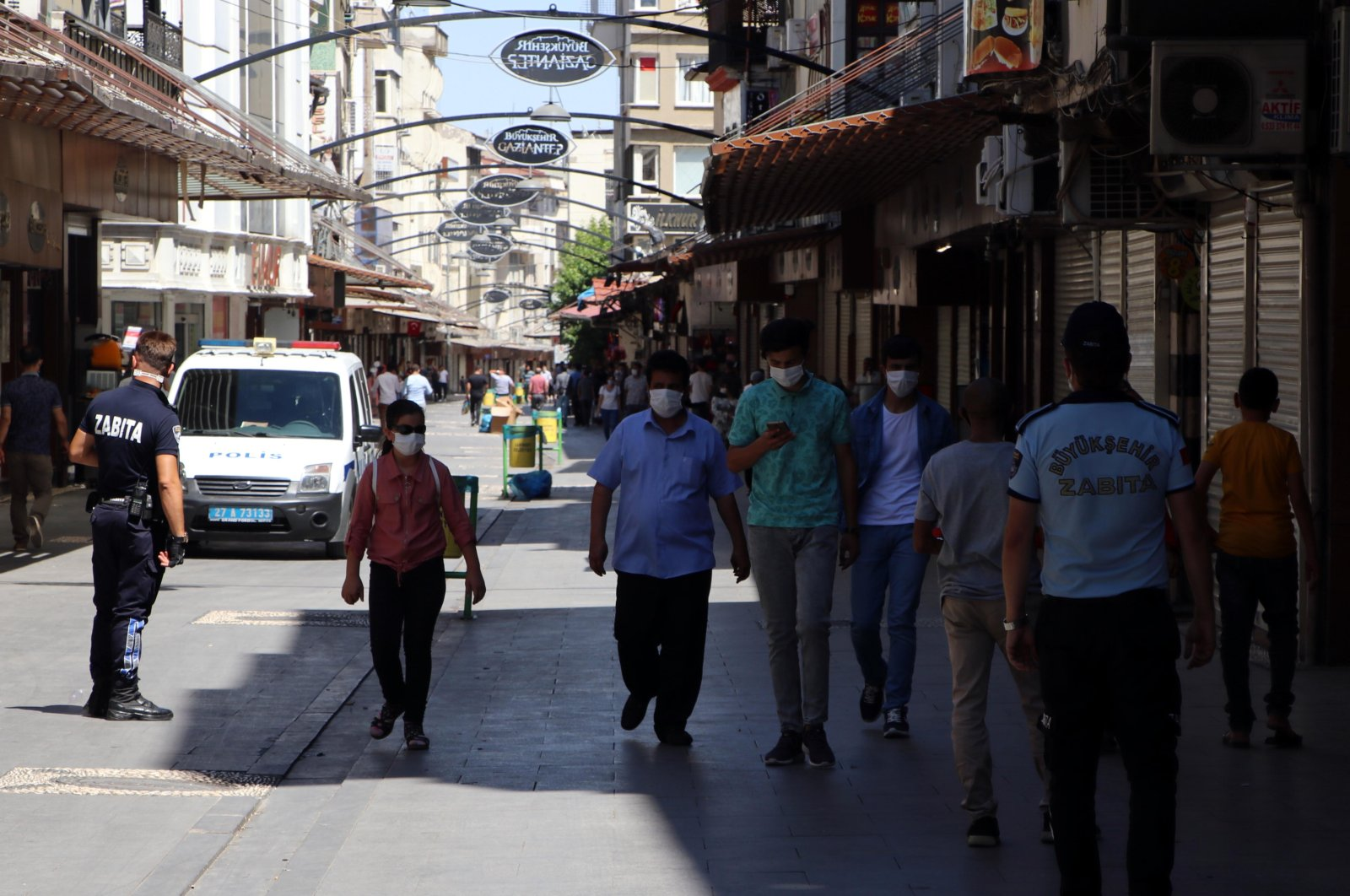 People wearing protective masks walk on a street in Gaziantep, southern Turkey, Aug. 2, 2020. (DHA Photo)