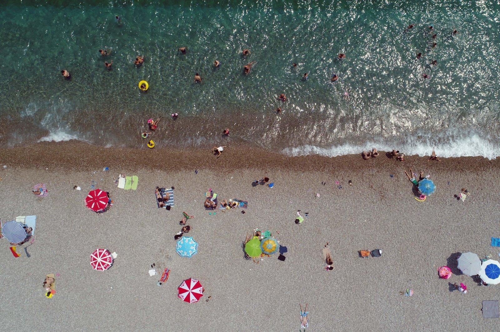 Holidaymakers enjoy the sun at Konyalatı beach in southern resort city Antalya, Turkey, Aug. 2, 2020. (DHA Photo)