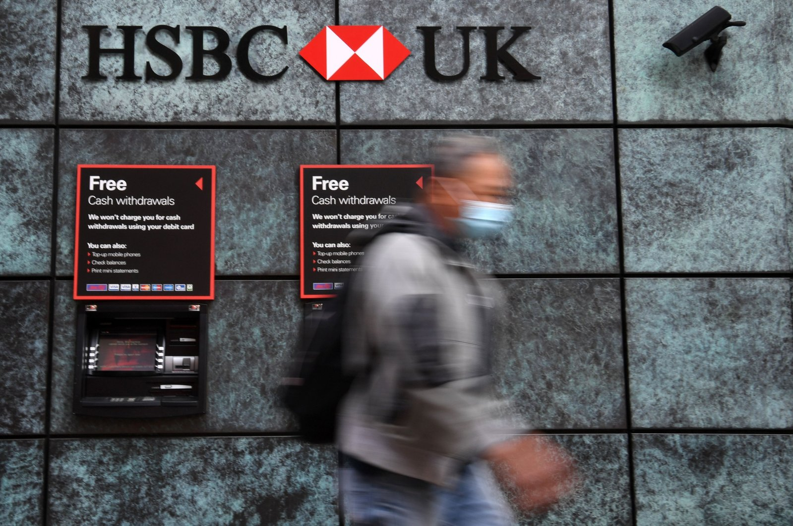 A pedestrian wearing a face mask due to the COVID-19 pandemic walks past a branch of an HSBC bank in central London, Aug. 3, 2020. (AFP Photo)