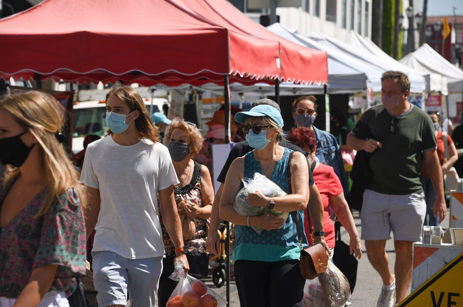 People wearing face coverings shop for fresh fruit, vegetables, flowers and meat at the Santa Monica Farmers' Market, Santa Monica, C.A., Aug.1, 2020. (AFP Photo)