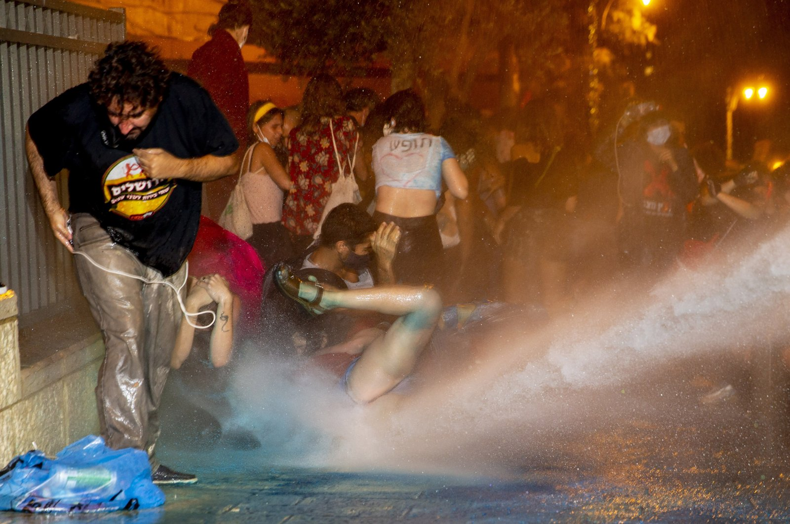 Police use a water cannon to disperse demonstrators during a protest against Israel's Prime Minister Benjamin Netanyahu outside his residence in Jerusalem, July 22, 2020. (AP Photo)