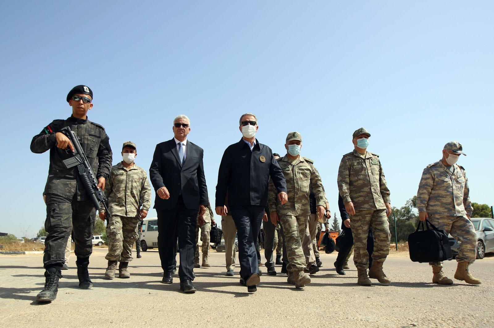Defense Minister Hulusi Akar walks alongside Libyan officials during a visit to Libya, July 6, 2020. (AA Photo)