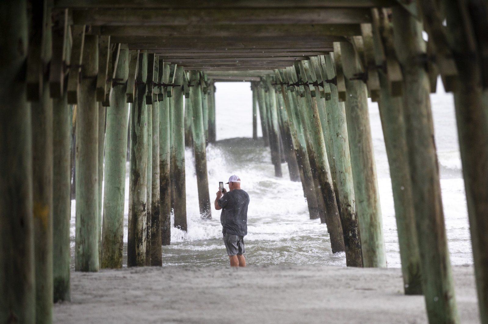 A person stands under the pier in Garden City, S.C., Monday, Aug. 3, 2020, as Isaias approached the Carolinas.  (The Sun News via AP)
