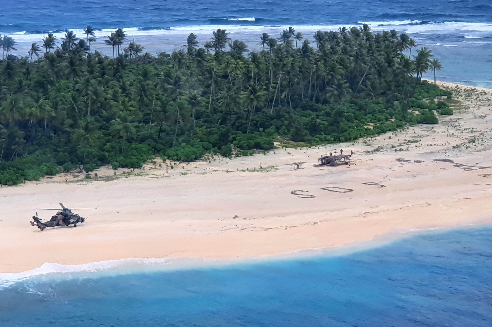 """An Australian Army ARH Tiger helicopter lands near the letters """"SOS"""" on a beach on Pikelot Island where three men were found in good condition after being missing for three days, Aug. 2, 2020. (Australian Defence Force Photo via AFP)"""