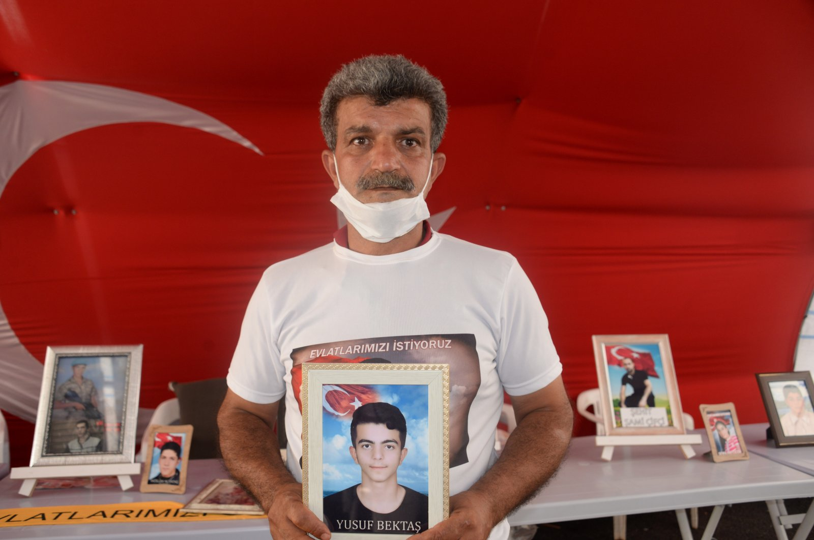 Father Celil Begdaş holds a picture of his son Yusuf in front of the Peoples' Democratic Party (HDP) headquarters in Diyarbakır, southeastern Turkey, July 31, 2020. (DHA Photo)