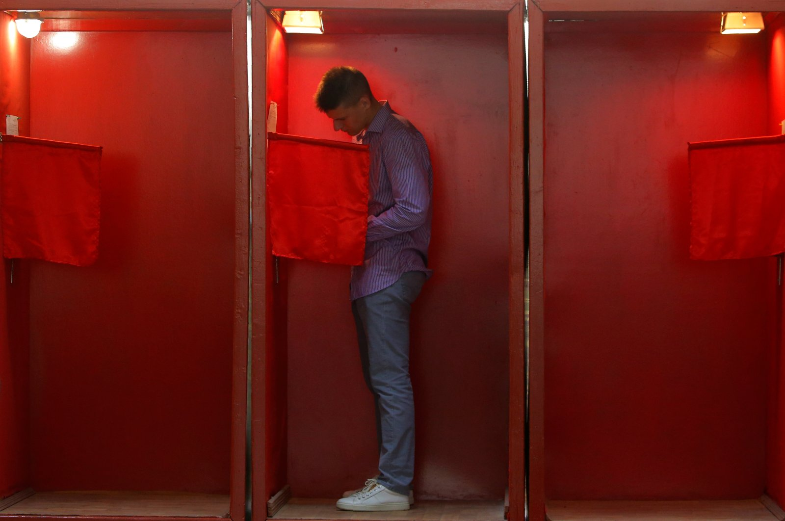 A man stands inside a voting booth during the early voting ahead of the Aug. 9 presidential election at a polling station in Minsk, Belarus, Aug. 4, 2020. (Reuters Photo)