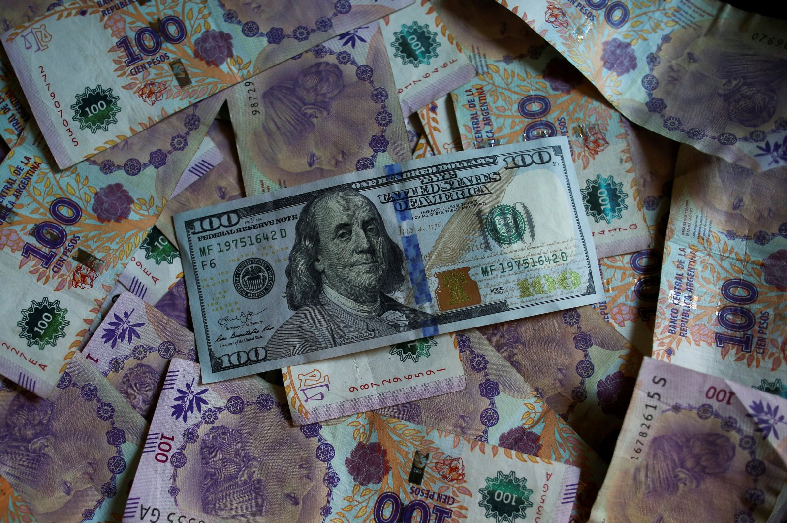 Argentine 100 peso bills sit underneath the United States 100 dollar bill in this picture illustration taken Sept. 3, 2019. (Reuters Photo)