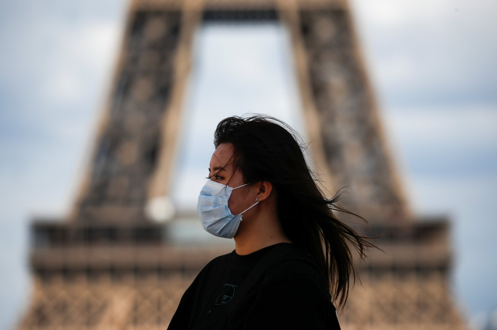 A woman wearing a protective face mask walks at the Trocadero square near the Eiffel Tower in Paris, Aug. 3, 2020. (Reuters Photo)