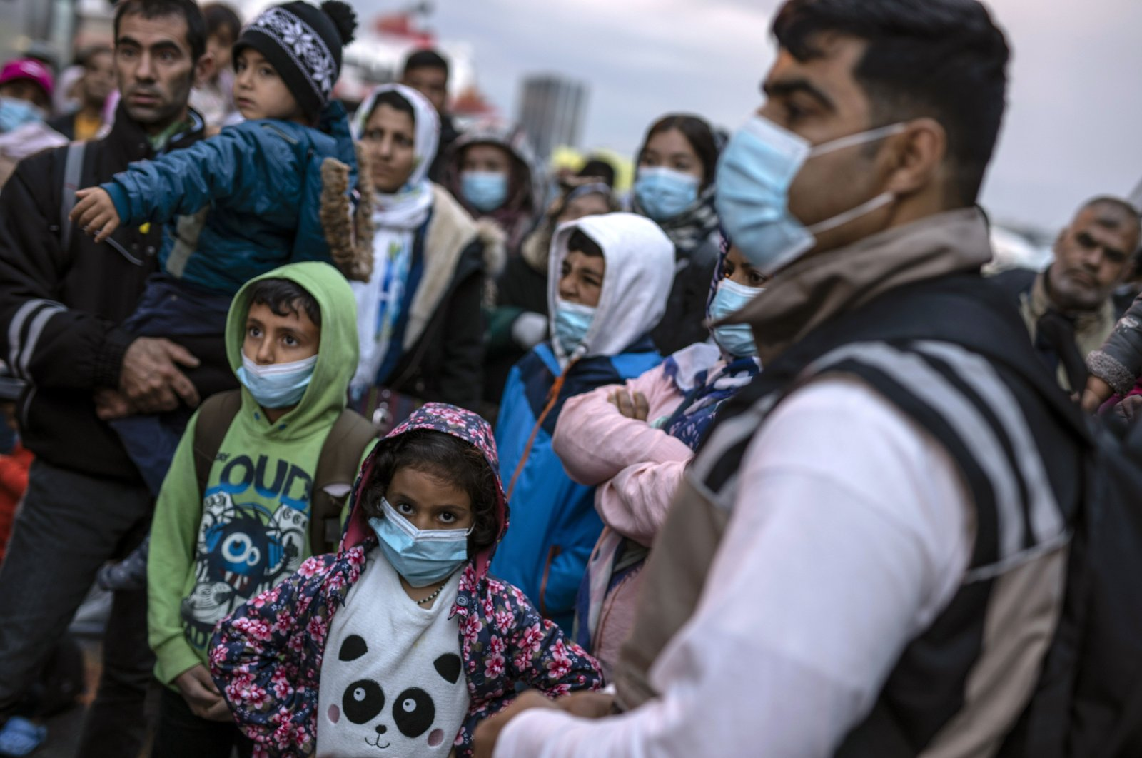 Refugees and migrants wearing masks to prevent the spread of the coronavirus, wait to get on a bus after their arrival at the port of Piraeus, near Athens, May 4, 2020. (AP Photo)
