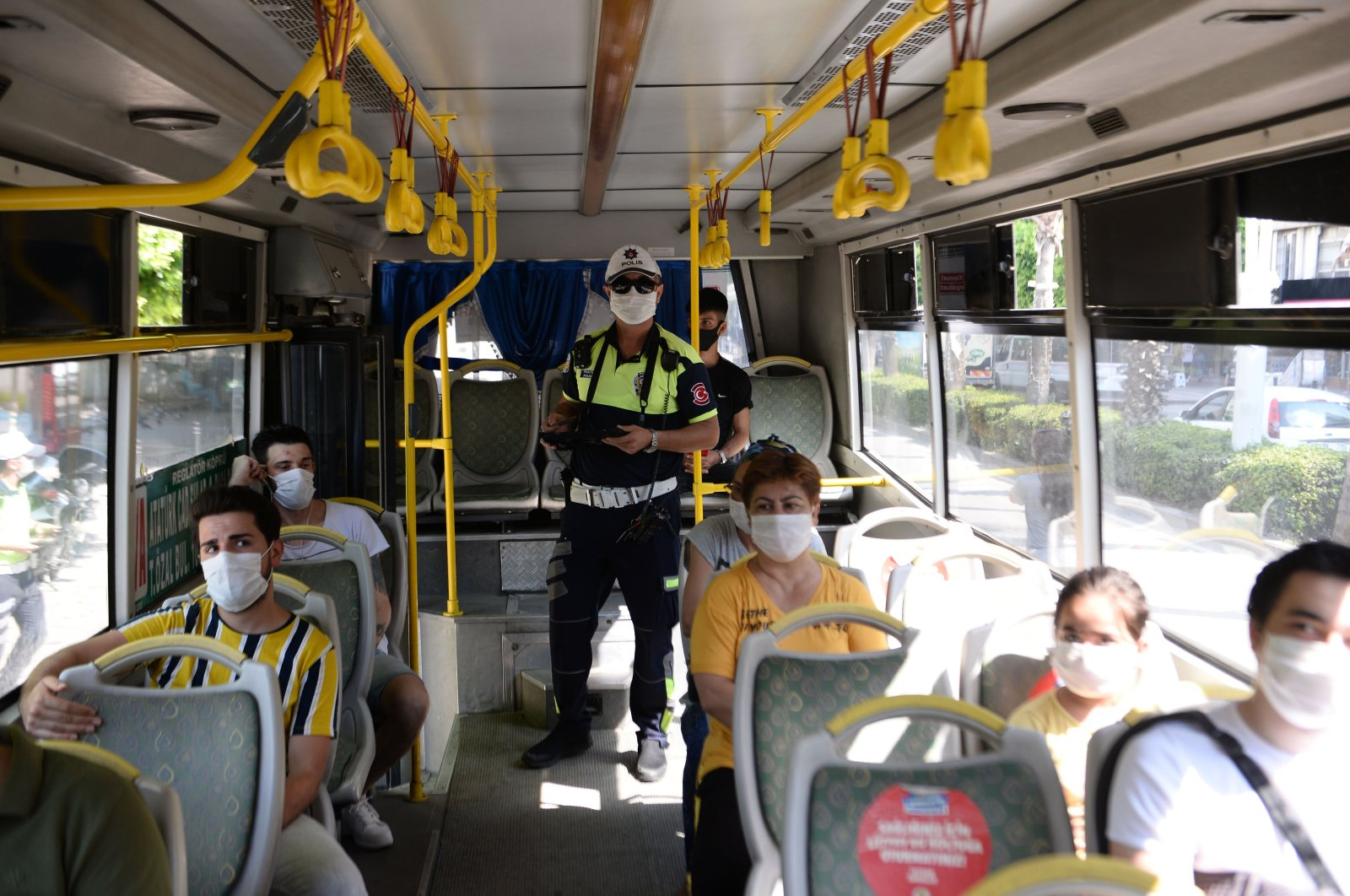 A police officer inspects coronavirus measures in a bus, in Adana, southern Turkey, Aug. 4, 2020. (DHA Photo)