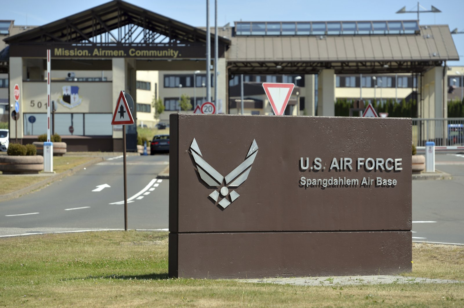 """A sign lettering """"U.S. Air Spangdahlem Force Air Base"""" displayed in front of an entrance of the U.S. military airport, Spangdahlem, July 30, 2020. (AP Photo)"""