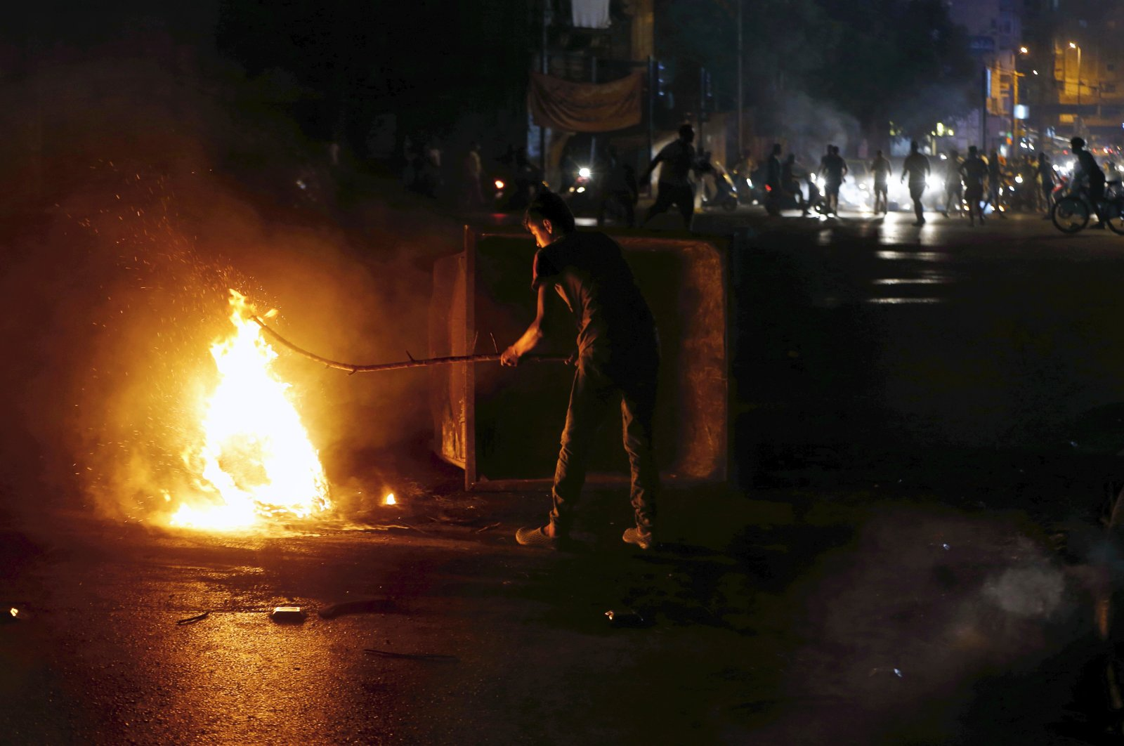 An anti-government demonstrator burns tires to block a road, Beirut, July 28, 2020. (AP Photo)