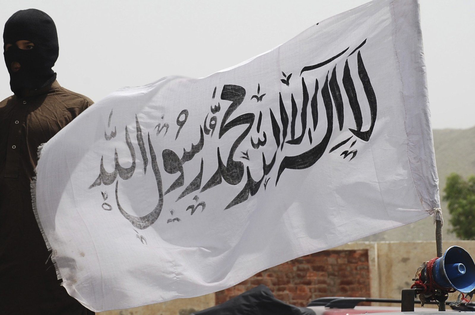 In this file photo, a white Taliban flag is seen beside a Pakistani Taliban fighter in the South Waziristan tribal region bordering Afghanistan, May 24, 2008. (Reuters Photo)