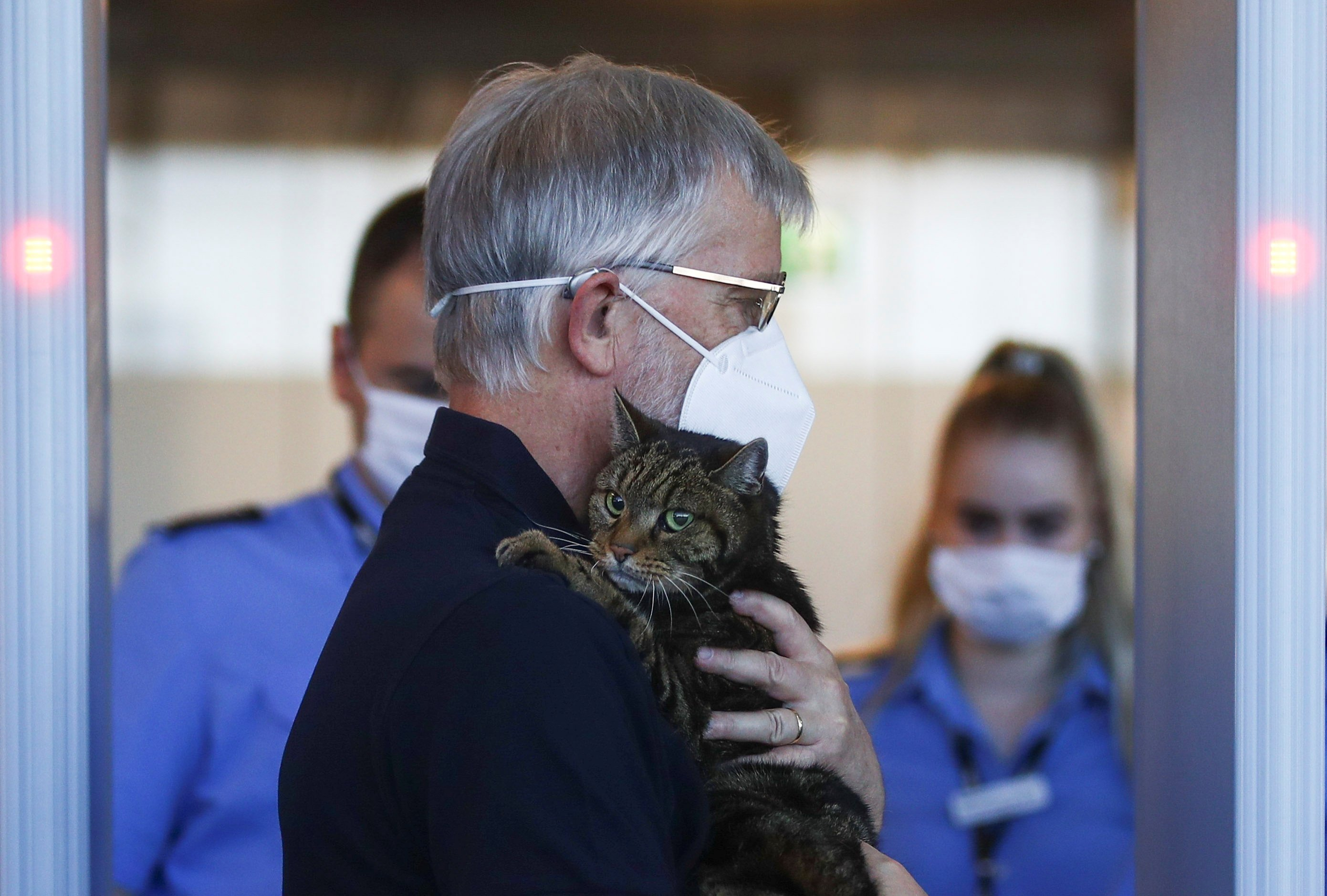 A man carrying a cat walks past security control at the Vienna International Airport in Schwechat, Austria, July 1, 2020. (Reuters Photo)