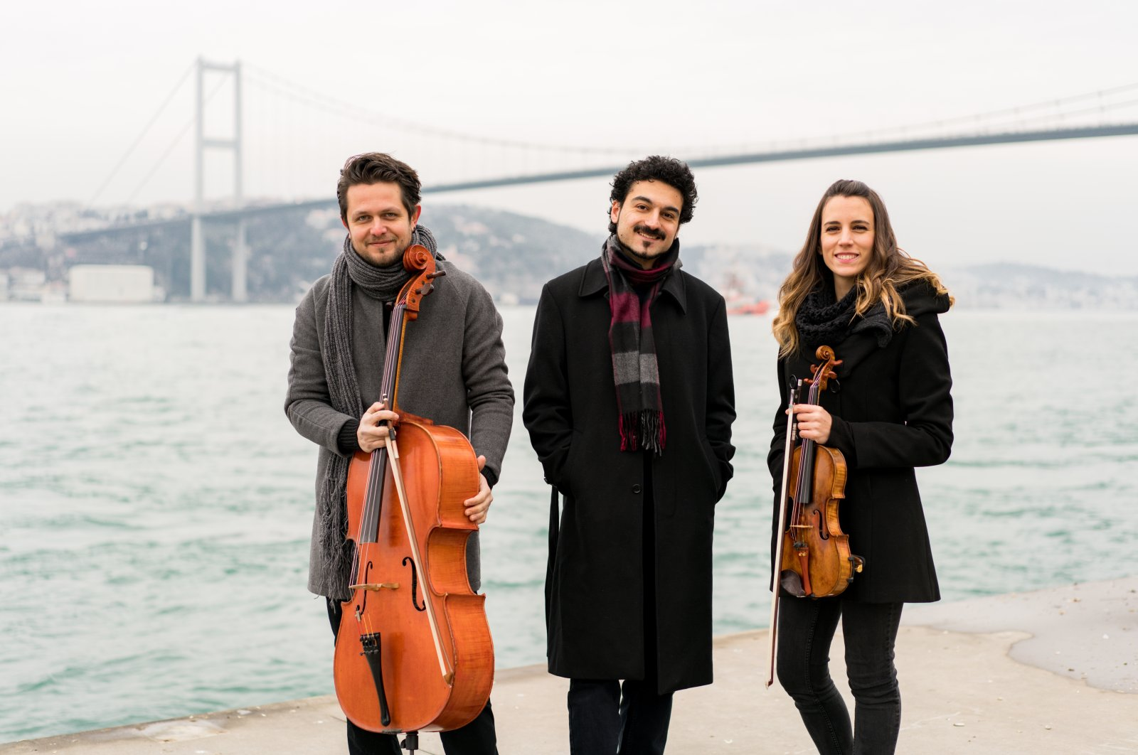 Çağlayan Çetin (L), Özgür Ünaldı (M) and Özgecan Günöz (R) pose in front of the Bosporus Bridge, Istanbul in this photo provided on Aug. 4, 2020.