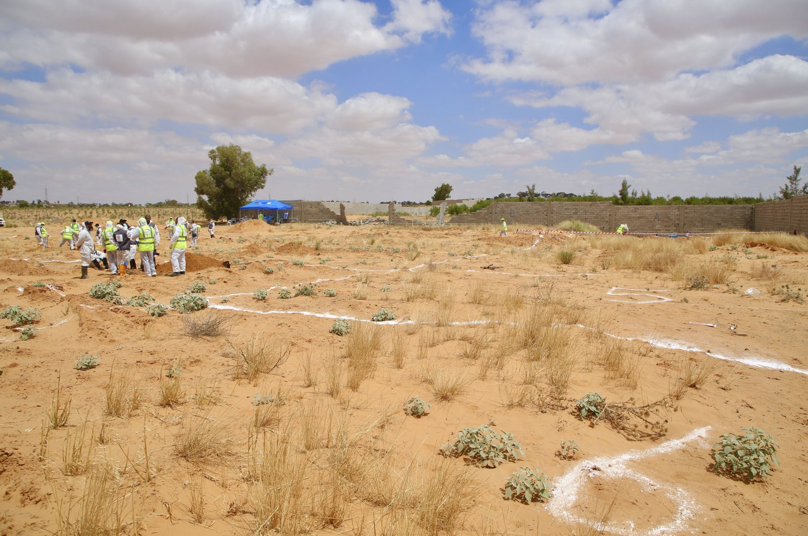 Libyan Ministry of Justice employees dig at the site of a suspected mass grave in the town of Tarhuna, Libya, June 23, 2020. (AP File Photo)