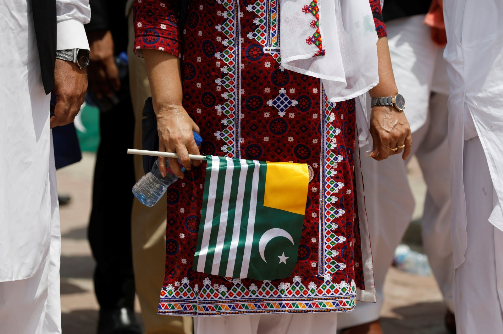 """A woman holds a flag as she observes one minute of silence with others to mark the """"Day of Exploitation in Kashmir,"""" one year after the Indian government split the state of Jammu and Kashmir into two federally controlled territories and took away its special privileges, during a walk in Karachi, Pakistan, Aug. 5, 2020. (Reuters Photo)"""
