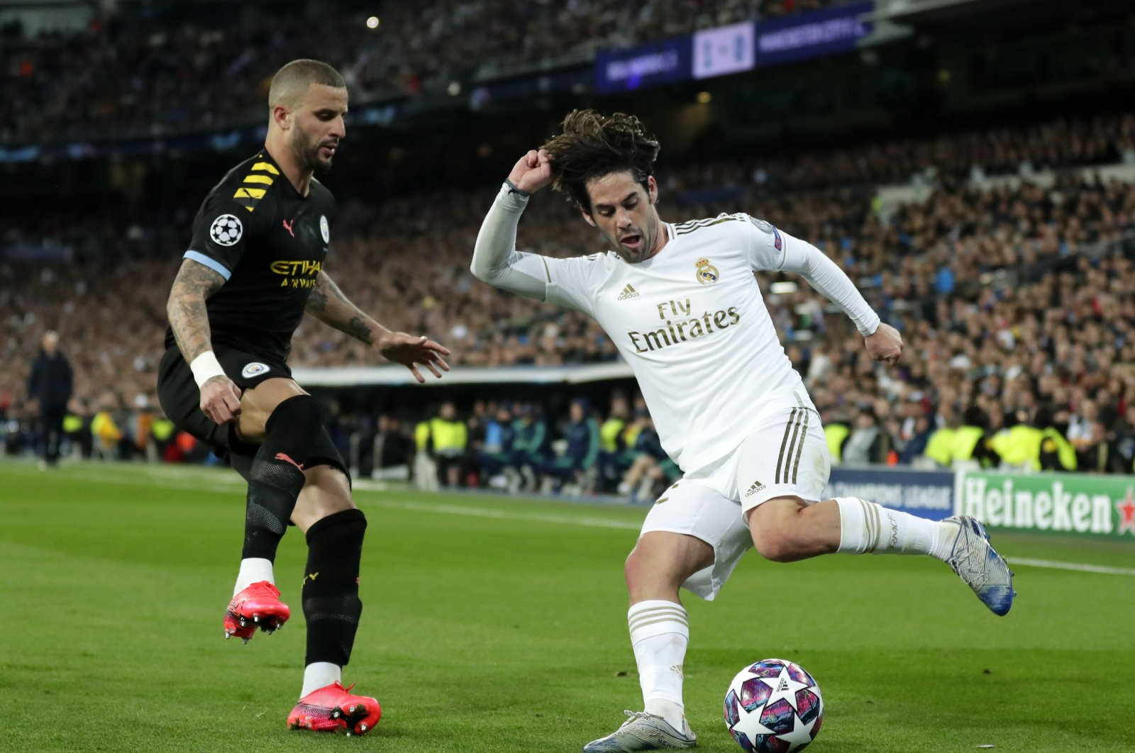 Real Madrid's Isco (R) duels for the ball with Manchester City's Kyle Walker during a Champions League match in Madrid, Spain, Feb. 26, 2020. (AP Photo)