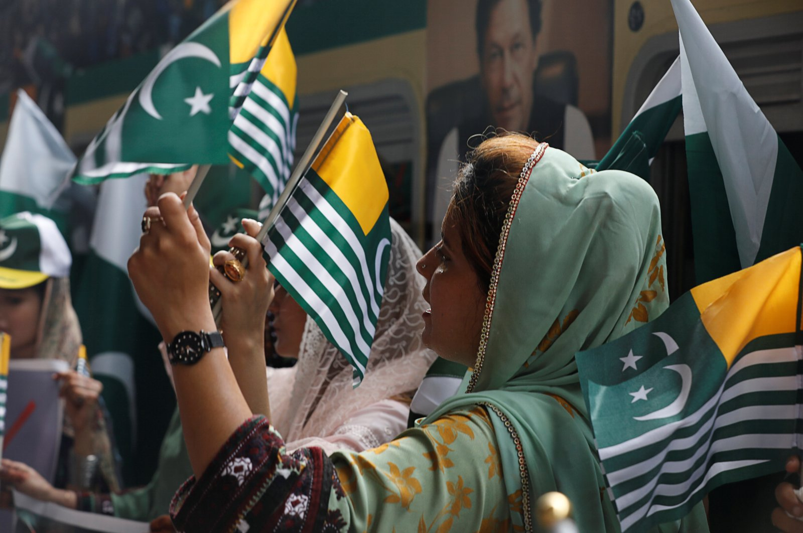 """A woman waves flags with others as they mark the """"Day of Exploitation in Kashmir"""" one year after the Indian government split the state of Jammu and Kashmir into two federally controlled territories and took away its special privileges, during a march in Karachi, Pakistan, Aug. 5, 2020. (Reuters Photo)"""