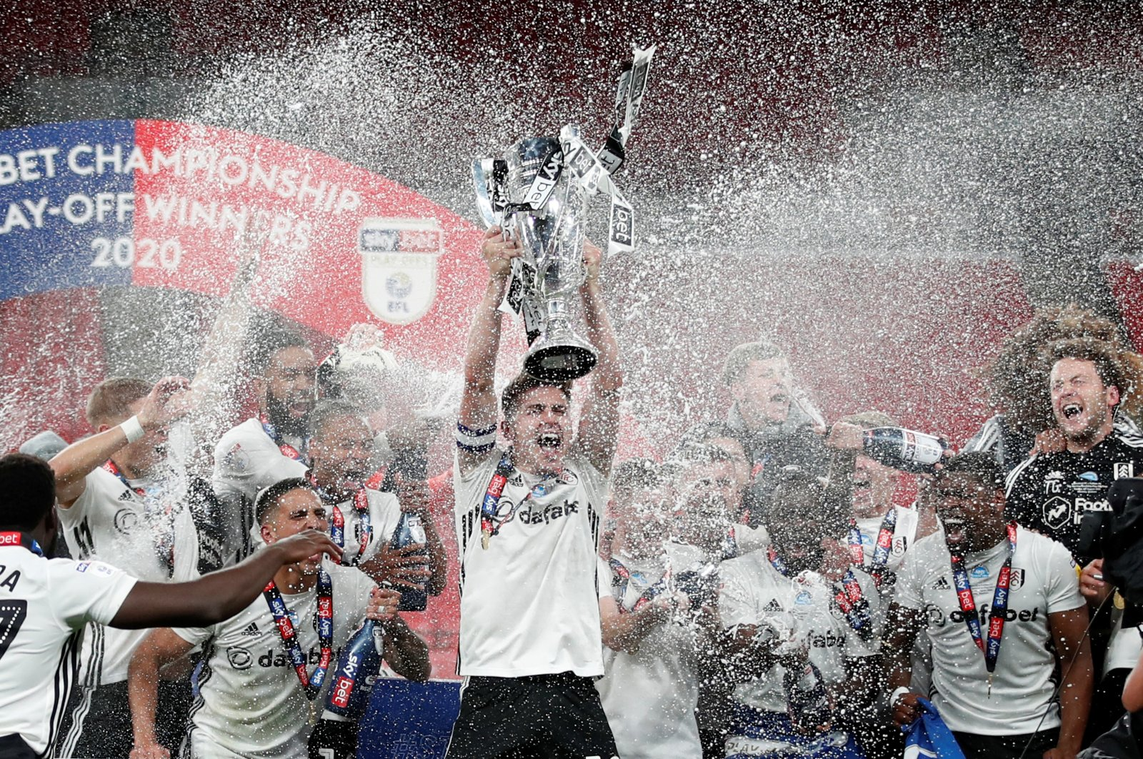 Fulham's Tom Cairney lifts EFL Championship trophy as he celebrates promotion to the Premier League with teammates after winning the playoff match against Bentford in London, Britain, Aug. 4, 2020. (Reuters Photo)