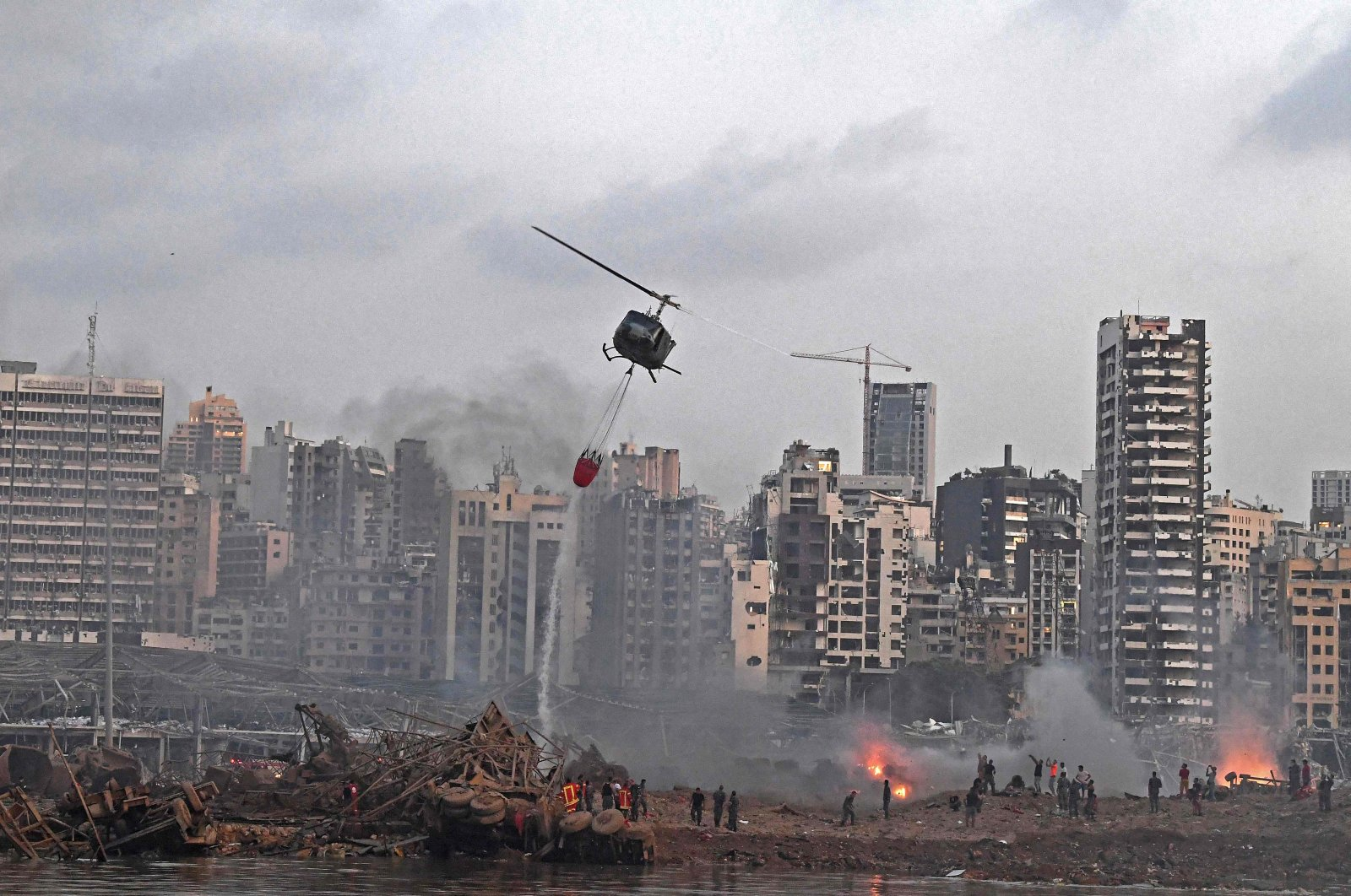A helicopter is dispatched to put out multiple fires at the scene of the massive explosion that hit a port in Beirut, Lebanon, Aug. 4, 2020. (AFP Photo)