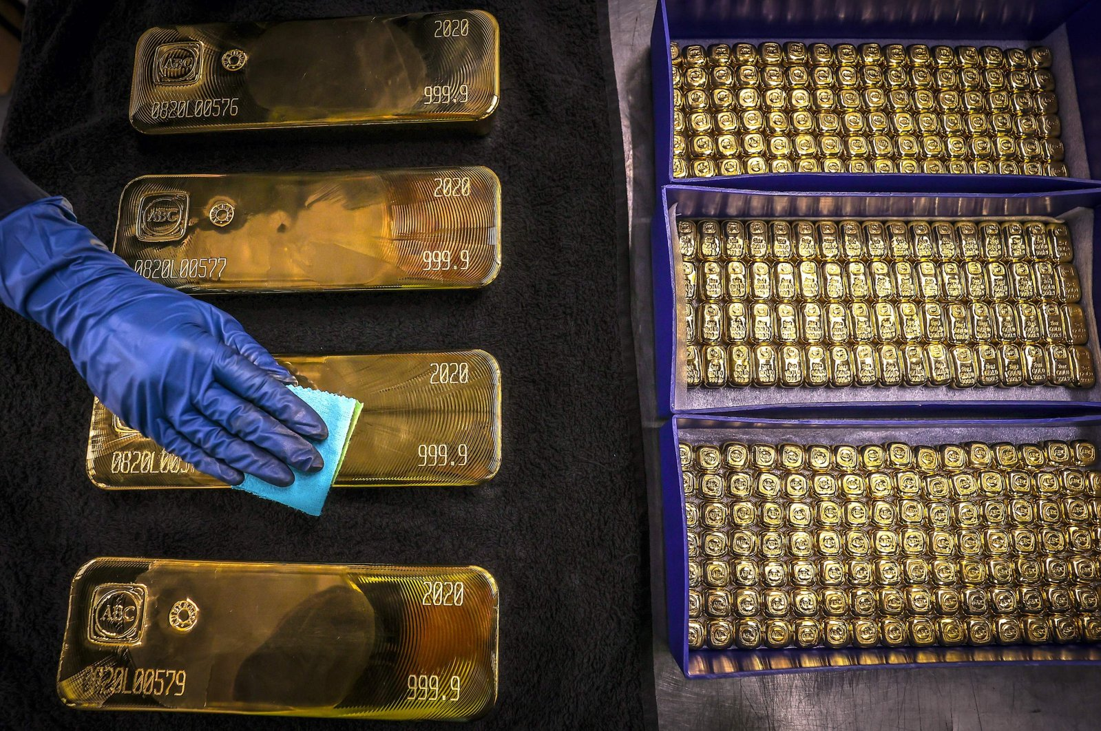A worker polishes gold bullion bars at the ABC Refinery in Sydney, Australia, Aug. 5, 2020. (AP Photo)