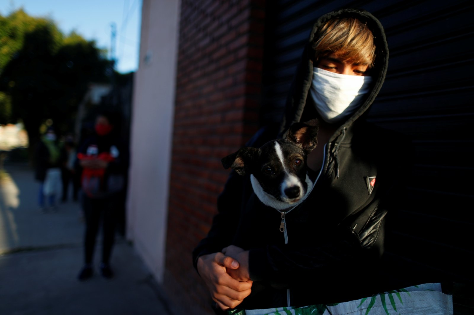 A boy holds his dog as he waits in line to receive a ration of stew at a soup kitchen during the COVID-19 outbreak, in Buenos Aires, Argentina, July 14, 2020. (Reuters Photo)